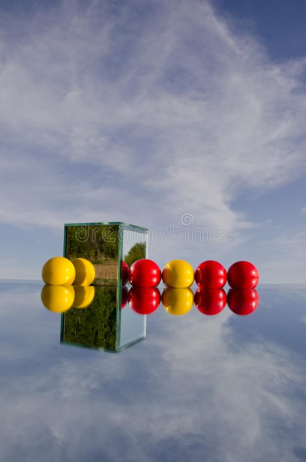 Red and yellow balls on mirror and sky