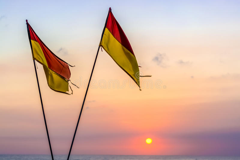 Red & yellow beach safety flags. That are crossed signalling that the beach is no longer being patrolled by life guards stock images