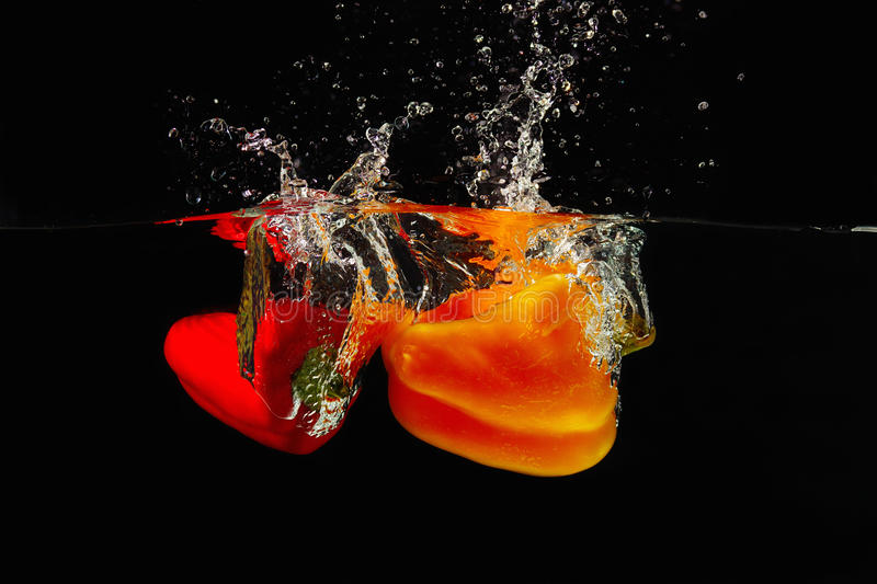 Red and yellow bellpepper falling into the water royalty free stock image