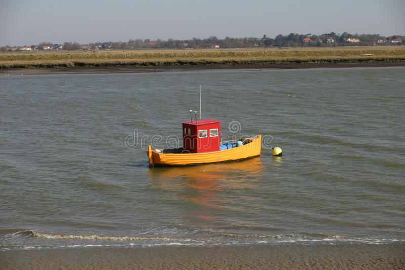 Colourful boat on river. Red and yellow brightly coloured small boat on a river with buildings and trees in the distant background stock photos
