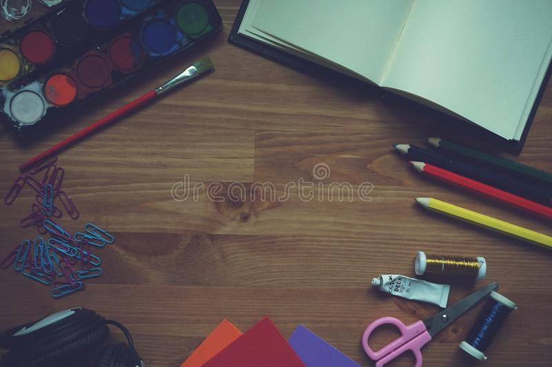 Red Yellow Blue Color Pencil Beside White Printer Paper on Brown Wood stock image