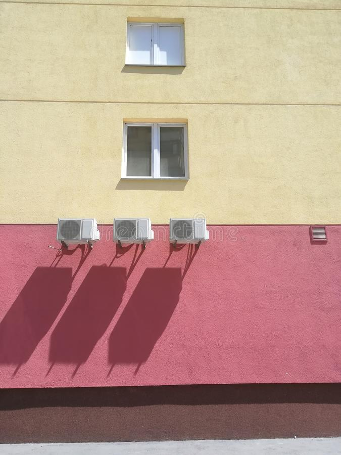 Red-yellow building with three air conditioners stock images
