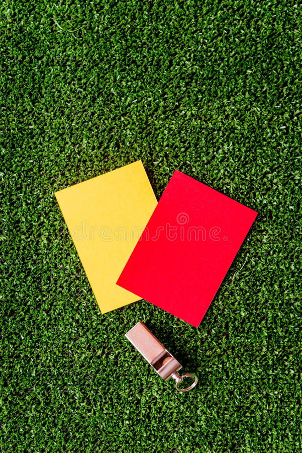 Red and yellow cards on green background top view. Mock up stock image