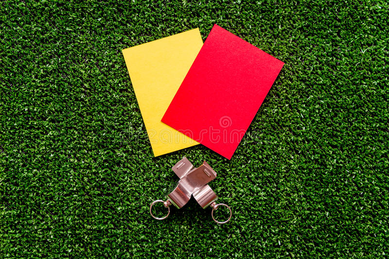Red and yellow cards on green background top view. Mock up royalty free stock photography