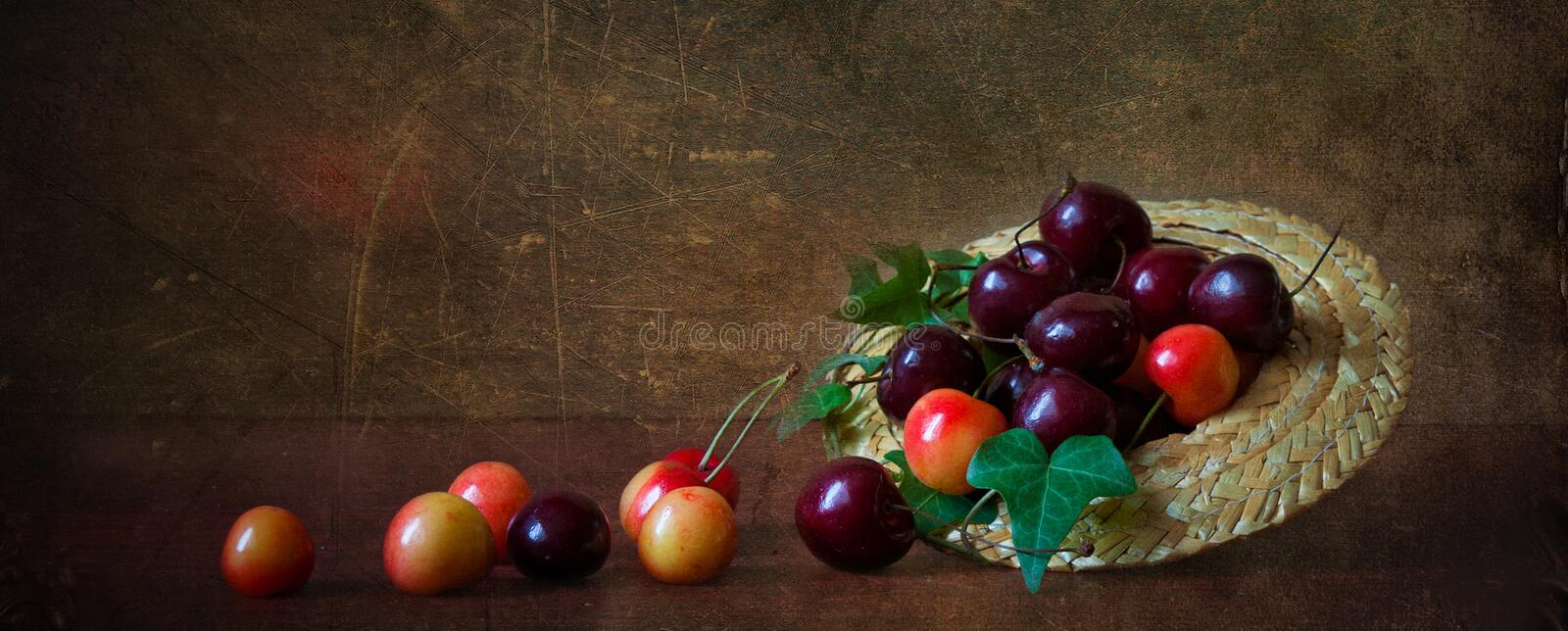 Red and yellow cherries in a small straw hat royalty free stock images