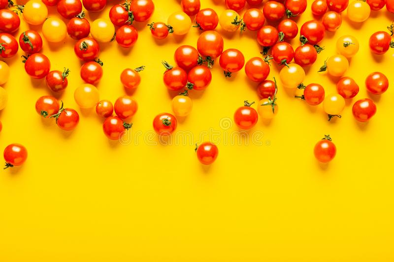Red and yellow cherry tomatoes on yellow background. Fresh bright organic vegetables royalty free stock images