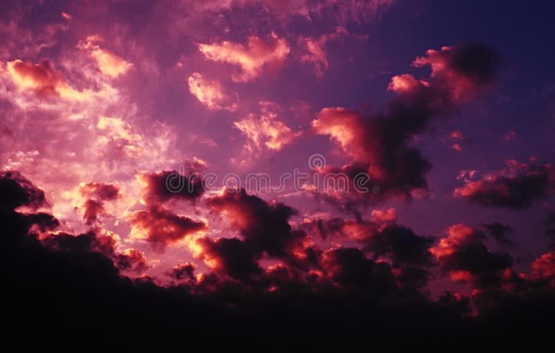 Red and yellow clouds illuminated by rising sun. Nature background - violet sky with red and yellow clouds illuminated by the rising sun. Photo taken with red stock image