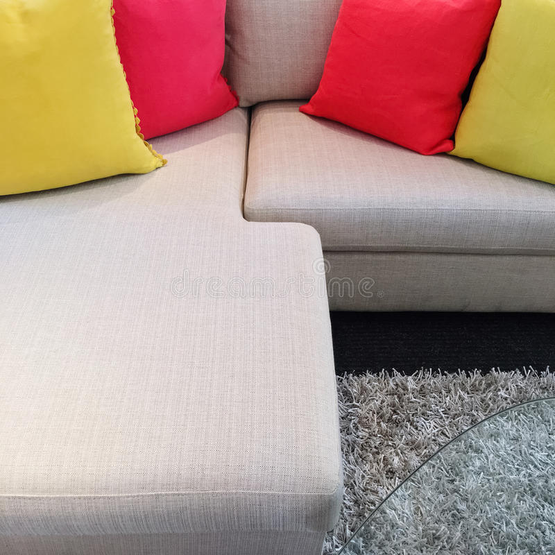 Red and yellow cushions on gray corner sofa. Bright red and yellow cushions decorating gray corner sofa royalty free stock images