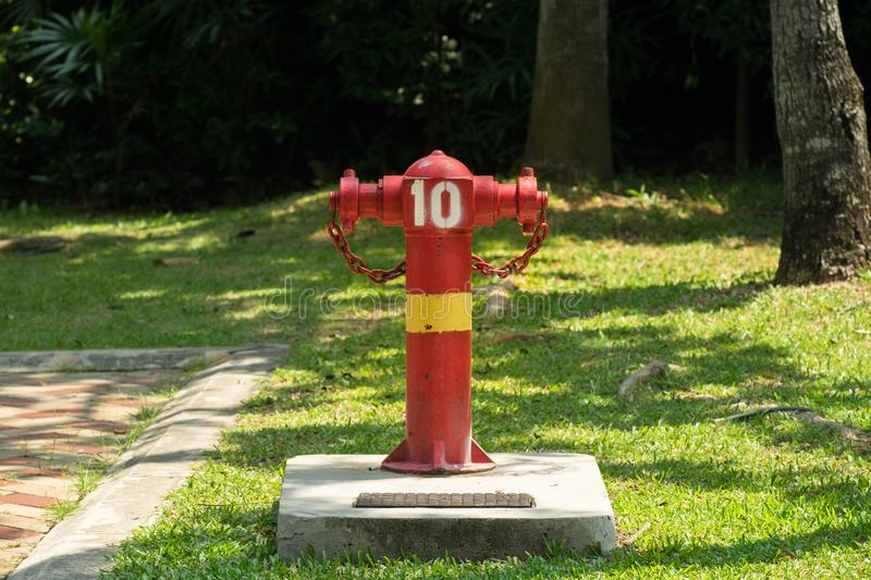 Red and Yellow Fire Hydrant in a park on a concrete. Called a fireplug or simply a plug, is a connection point by which firefighters can tap into a water stock photography