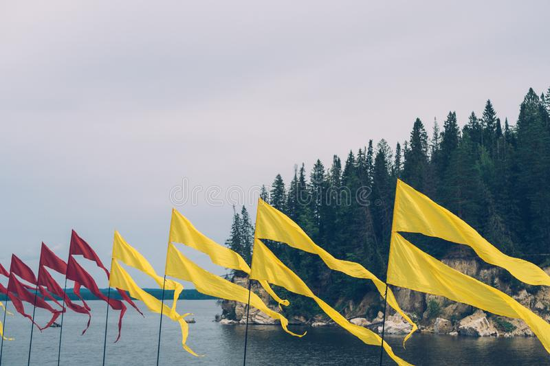 Red and yellow flying flags at river`s bank against rocks, dark forest and grey sky. Colourful flags on flagpoles at river`s bank during summer open-air stock photos