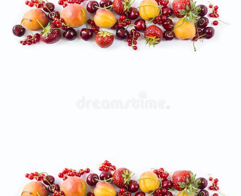 Red and yellow fruits on white background. Ripe apricots, red currants, cherries and strawberries. Sweet and juicy fruits at bord royalty free stock image