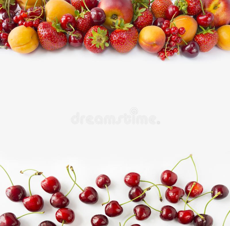 Red and yellow fruits on white background. Ripe apricots, red currants, cherries and strawberries. Sweet and juicy fruits at bord stock photos