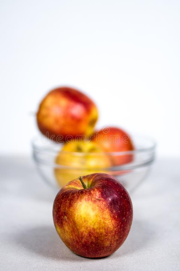 Red Yellow Gala Apple in Front of Glass Fruit Bowl royalty free stock photo