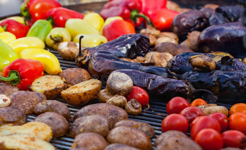 Red, yellow, green bell peppers, potatoes, mushrooms, tomatoes and eggplant grilled until golden brown. The concept of proper nutrition and a healthy lifestyle royalty free stock photography