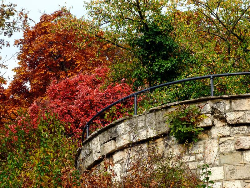 Red, yellow and green autumn foliage with stone turret. Red, yellow and green dense autumn foliage on hill side with round stone fort like turret detail. black royalty free stock image