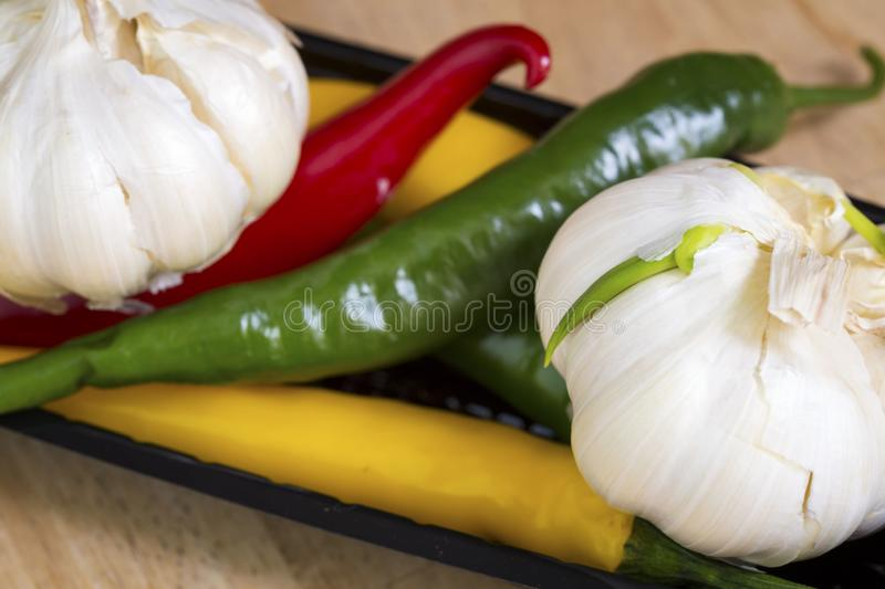 Red, yellow and green hot pepper and garlic.  stock images
