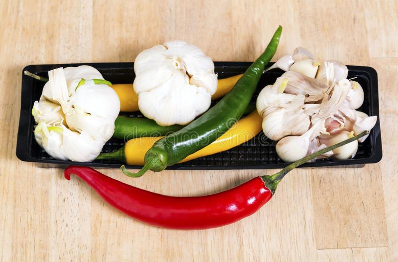 Red, yellow and green hot pepper and garlic.  stock image