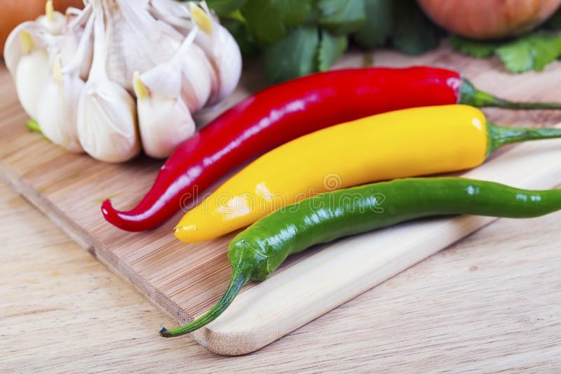 Red, yellow and green hot pepper and garlic. On wooden background stock photography
