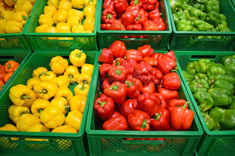 Red, yellow and green peppers in a plastic box on a store counter. royalty free stock image