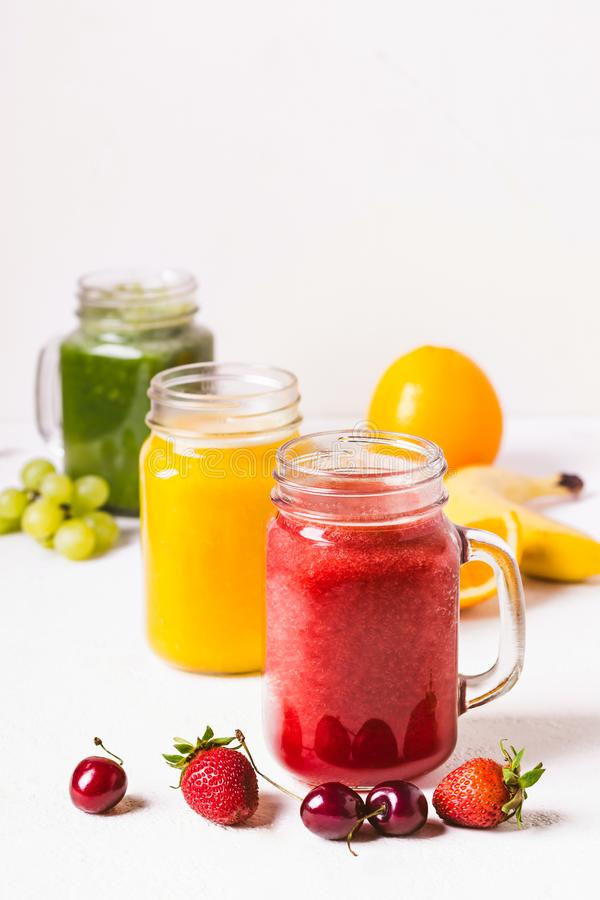 Red, yellow and green smoothie in a glass jar and ingredients royalty free stock image