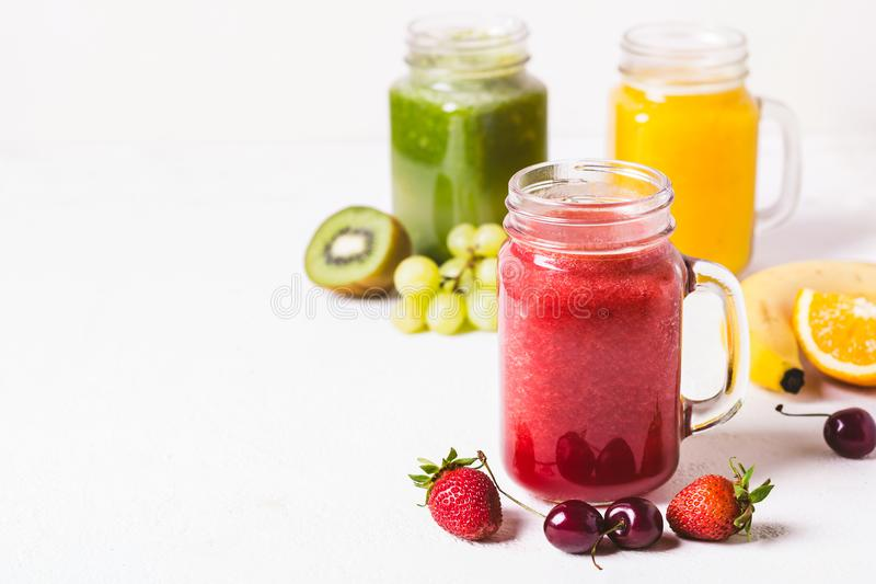 Red, yellow and green smoothie in a glass jar and ingredients royalty free stock photography