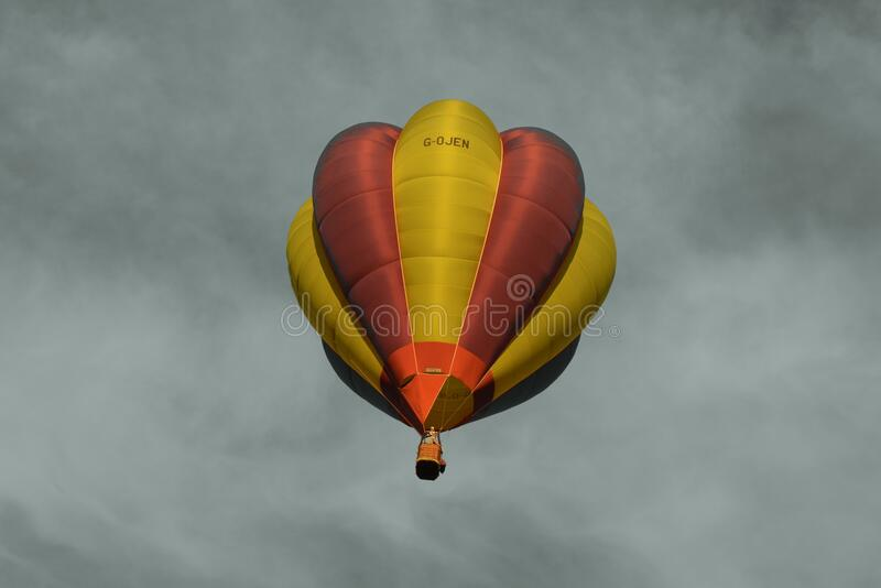 Red and Yellow Hot Air Balloon Under Sea of Clouds royalty free stock photos