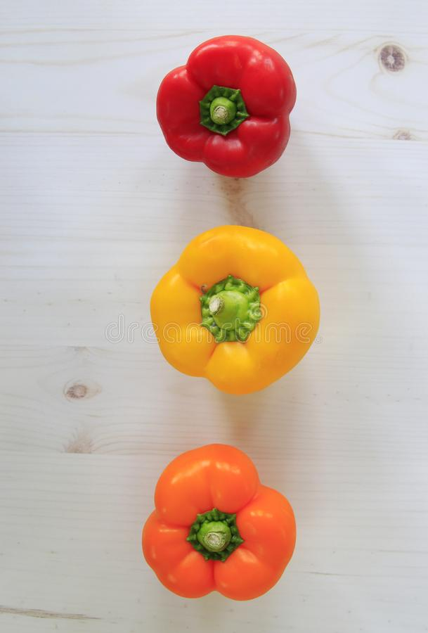 Red, yellow and orange bell peppers lined up on plank background. Flat lay stock image