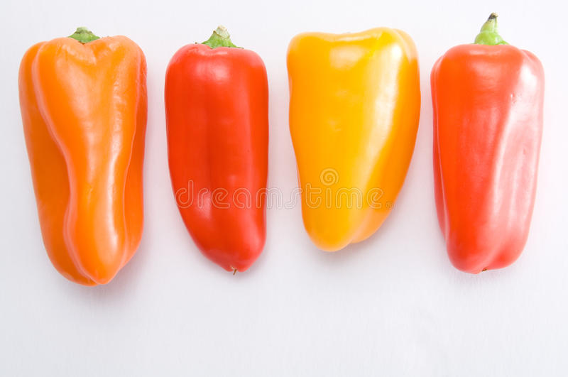 Red, Yellow and Orange Sweet Peppers on White stock photos