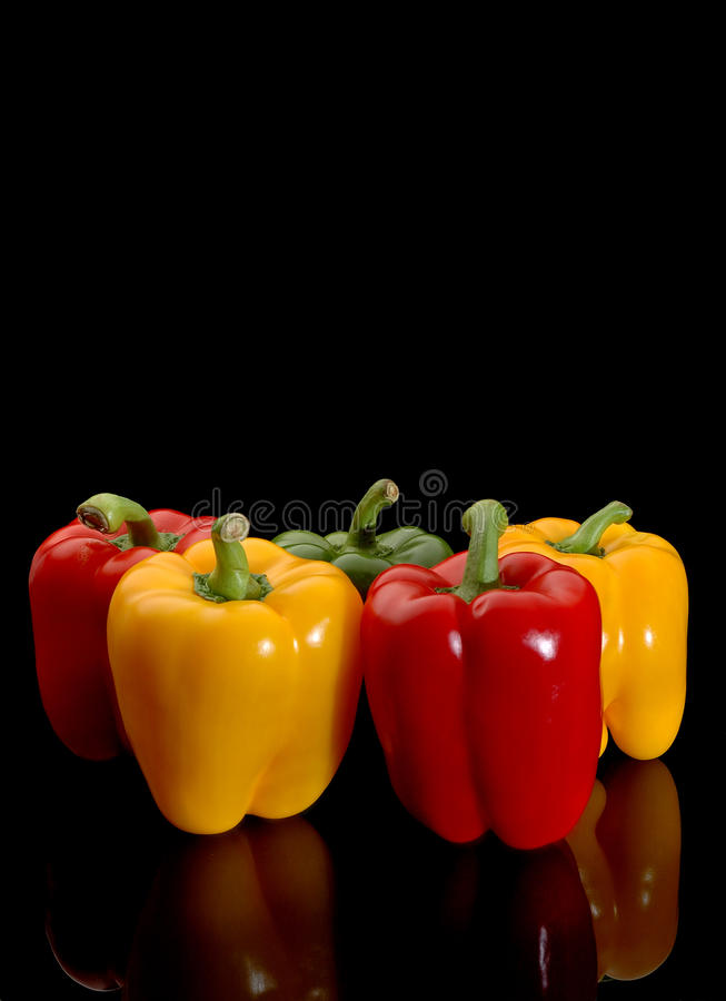 Red and yellow peppers. Red and yellow bell peppers with reflection isolated against a black background royalty free stock image