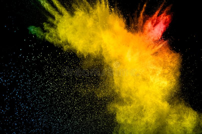 Red yellow  powder explosion on black background.Red yellow color dust splash clouds royalty free stock photography