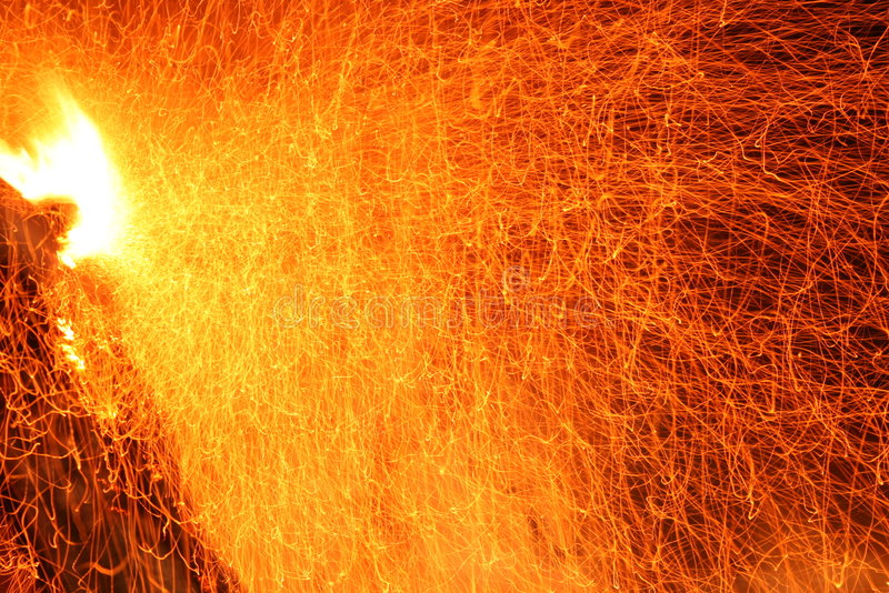 Red and yellow sparks. These sparks were generated by a blow on the burning wood. Here you can see the source of sparks, which is white. In this picture there royalty free stock image