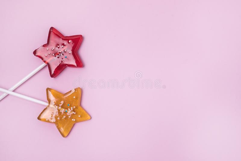 Red and Yellow Stars Shaped Lollipop on Light Pink Background Homemade Fruit Lollipop Candy Background Flat Lay Top View Copy. Space royalty free stock images