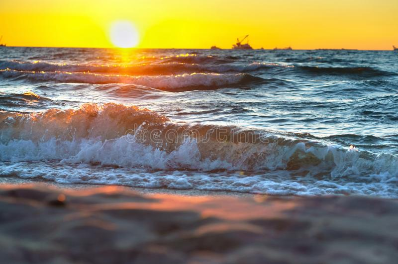 Red yellow sunset on the sea shore, in the surf of the waves of the Baltic sea, a magnificent sunrise. In the surf of the waves of the Baltic sea, a magnificent stock image