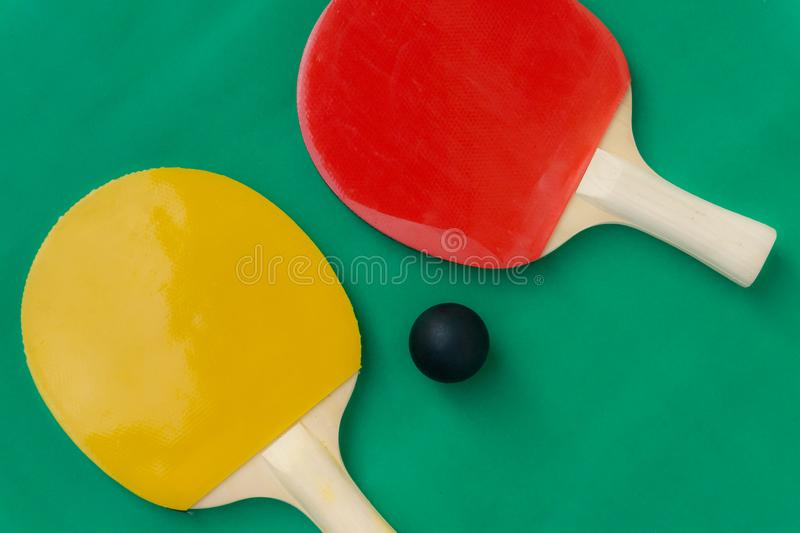 Red and yellow table tennis rackets with black balls,.table tennis rackets and balls on table.  stock photo