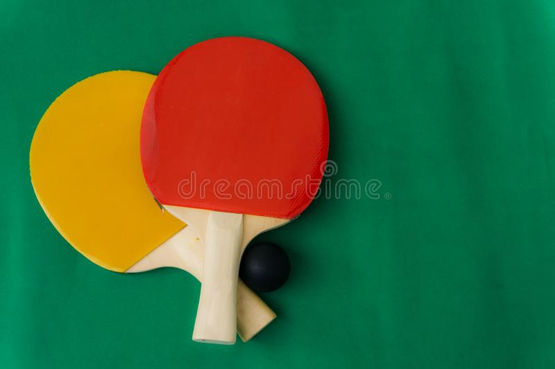 Red and yellow table tennis rackets with black balls,.table tennis rackets and balls on table. Red and yellow table tennis rackets with black balls,table tennis stock photography