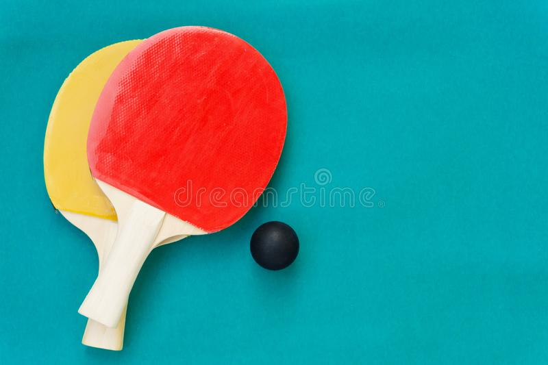 Red and yellow table tennis rackets with black balls,.table tennis rackets and balls on table. Red and yellow table tennis rackets with black balls,table tennis stock photos