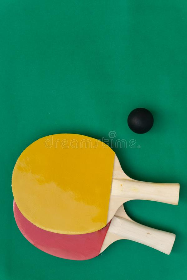 Red and yellow table tennis rackets with black balls,.table tennis rackets and balls on table. Red and yellow table tennis rackets with black balls,table tennis royalty free stock images