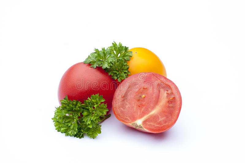 Red and yellow tomato and parsley on the white isolatd background stock photo