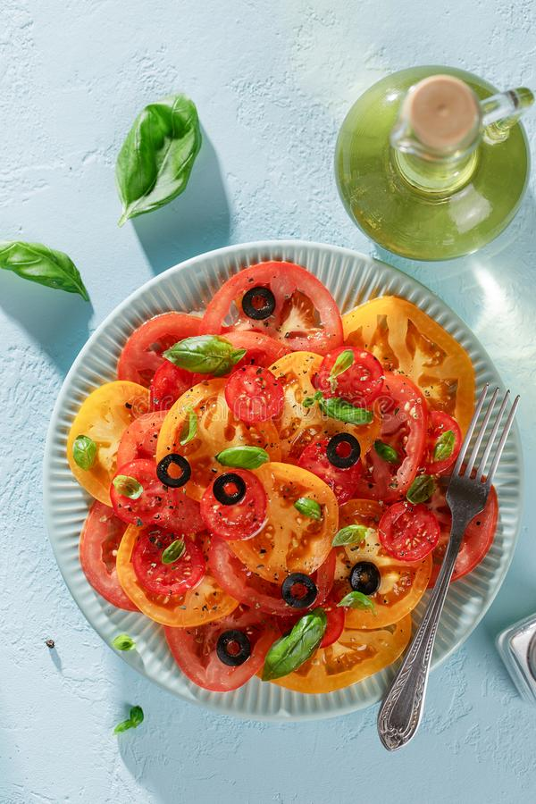 Red and yellow tomato slices with basil and olives on the plate on blue table. royalty free stock images