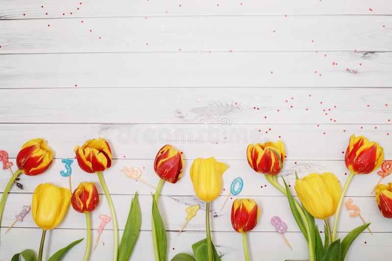 Red, yellow tulips flowers, candle and confetti in wooden background. royalty free stock photos