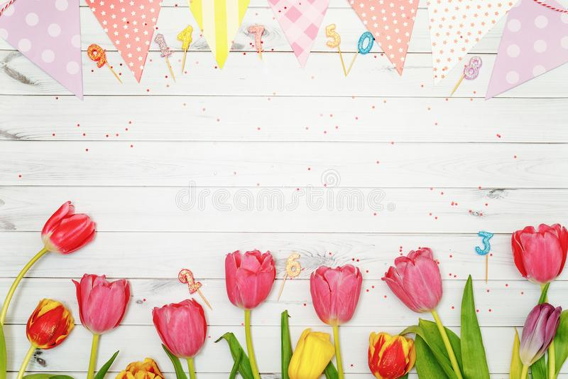 Red, yellow tulips flowers, candle and confetti in wooden background. stock photo