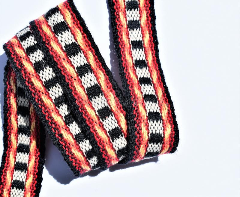 Colorful, patterned and handwoven strap. Weaving. Wool. Red. yellow, white and black wool handwoven functional strap which could be used as a belt or guitar stock images