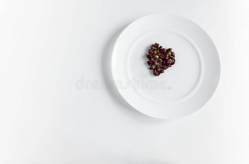 Red young roses in the shape of a heart. Buds of red young roses on a white plate for food background white shape heart royalty free stock image