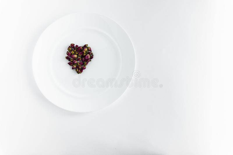 Red young roses in the shape of a heart. Buds of red young roses on a white plate for food background white shape heart stock photography
