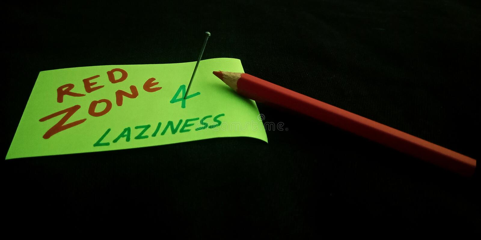 Red zone for laziness text written on black background with pencil. Lazy, people, not, allowed, concept, brain, sentence, reveal, time, displayed, pink, colour stock image