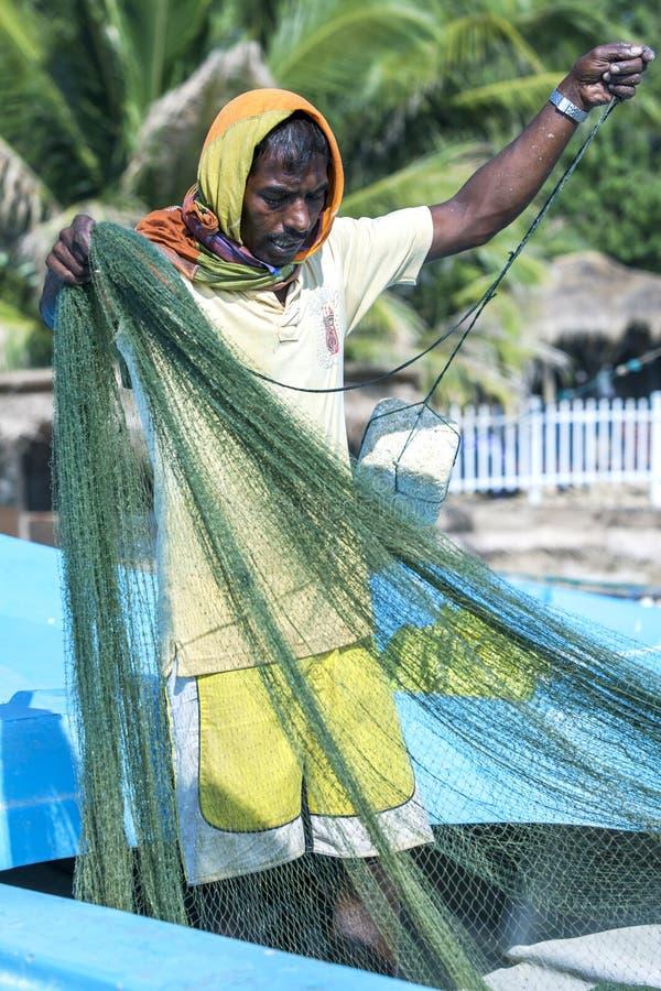 Reda ut för fiskare som är hans, förtjänar på den Arugam fjärdstranden i Sri Lanka fotografering för bildbyråer