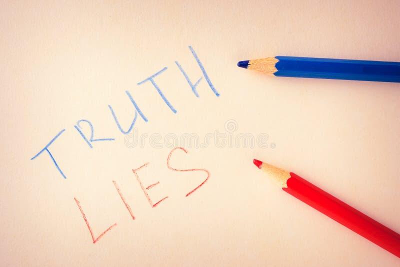 Redacta la verdad y las mentiras, escritas en lápices coloreados en el papel imagenes de archivo