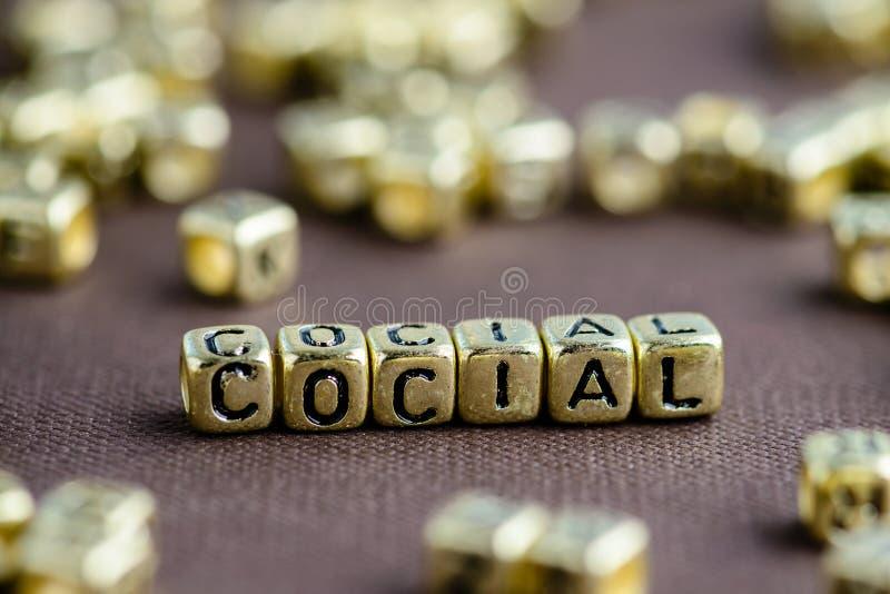 Redacte al SOCIAL hecho de pequeñas letras de oro en el backgrou marrón imagen de archivo