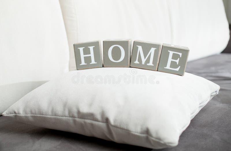 Redacte a casa deletreado en los bloques de madera que mienten en el sofá foto de archivo libre de regalías