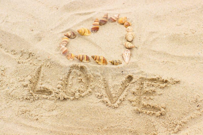 Redacte el amor escrito en la arena en la playa, corazón de cáscaras fotos de archivo